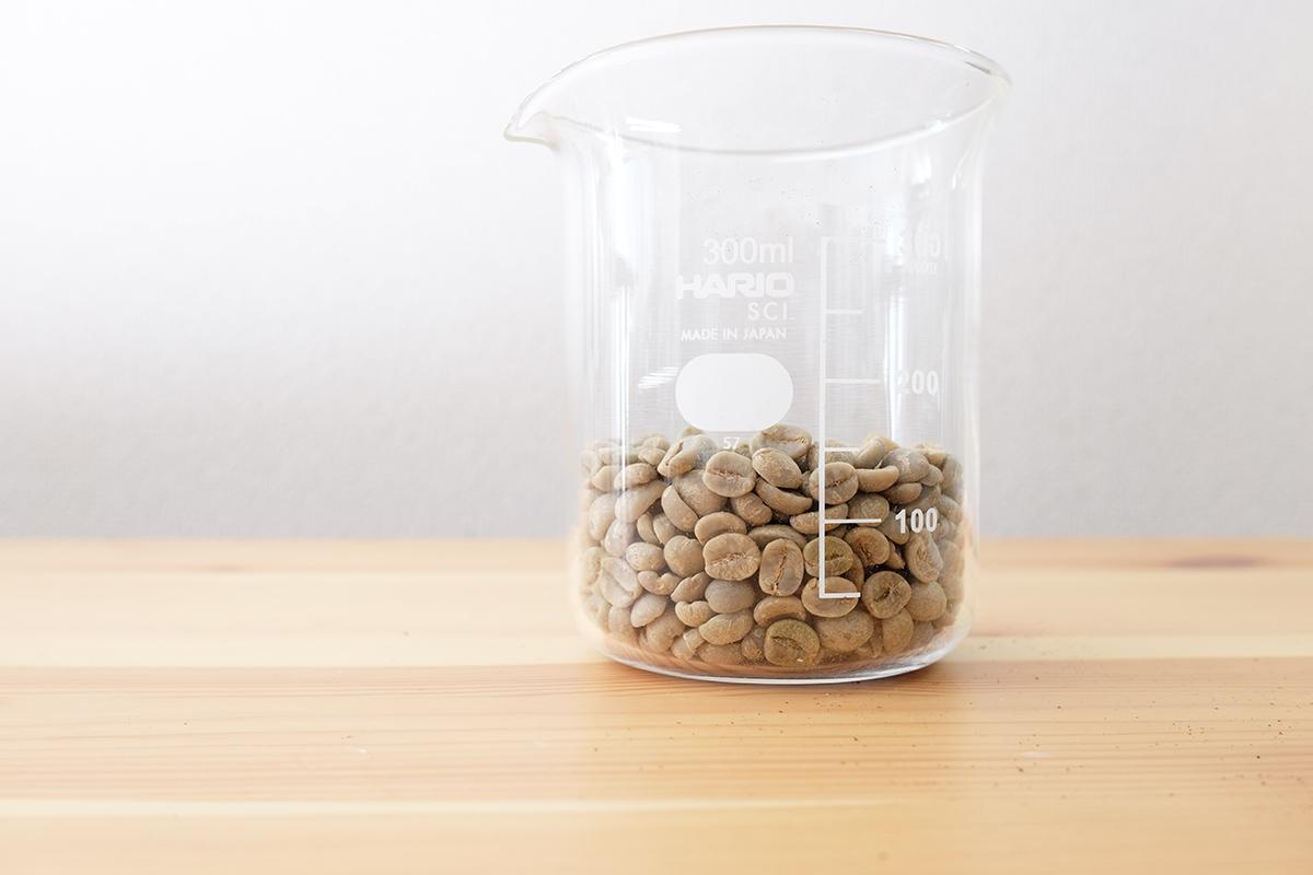 ビーカーに入ったコーヒー生豆
