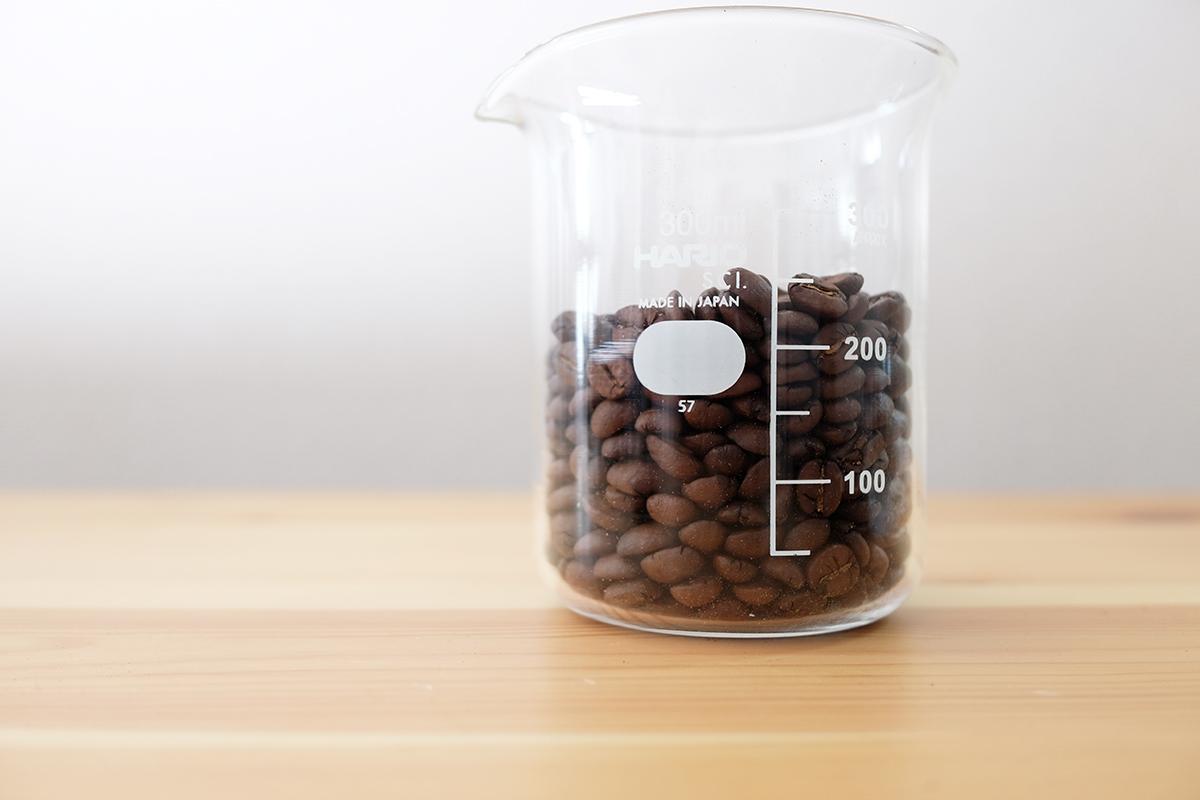 ビーカーに入った深煎りコーヒー豆