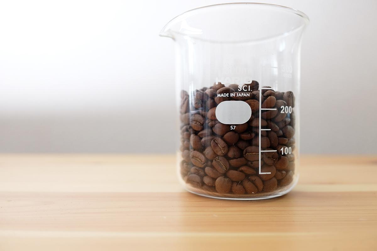ビーカーに入った浅煎りのコーヒー豆