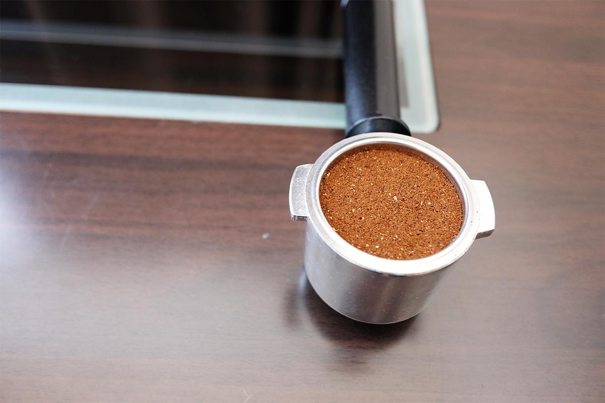 タンピングした浅煎りのコーヒー粉が入ったポルタフィルター