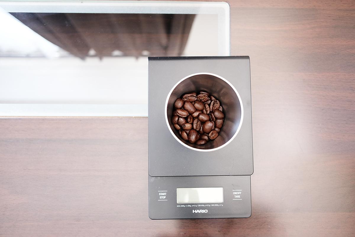ドリップスケールの上に乗ったカップに入ったコーヒー豆