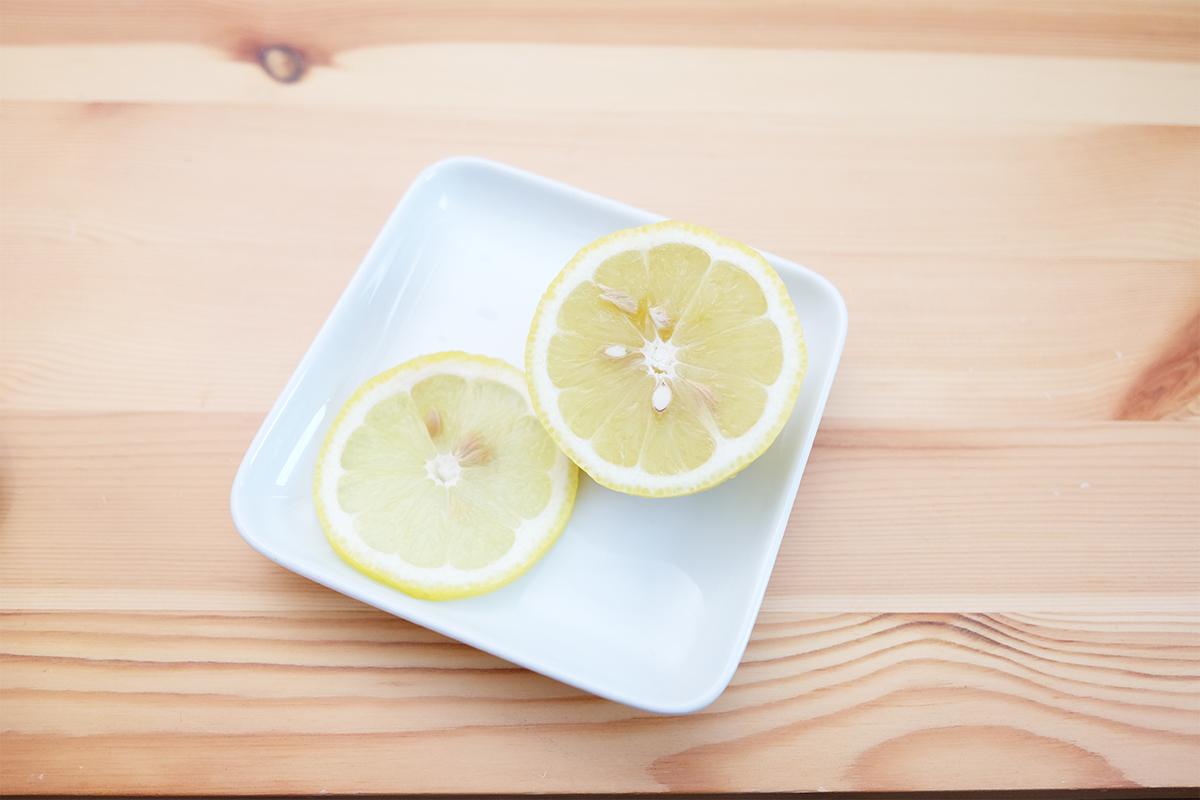 皿に乗った輪切りのレモンと大きくカットしたレモン