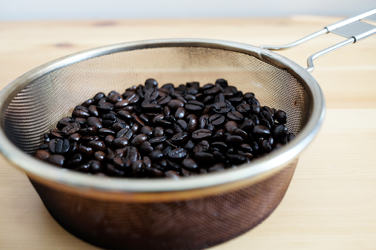 手網に入った焙煎したコーヒー豆