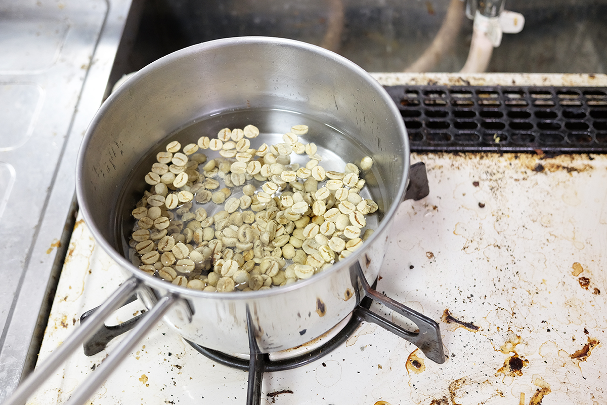 水を張った小鍋に入ったコーヒー生豆